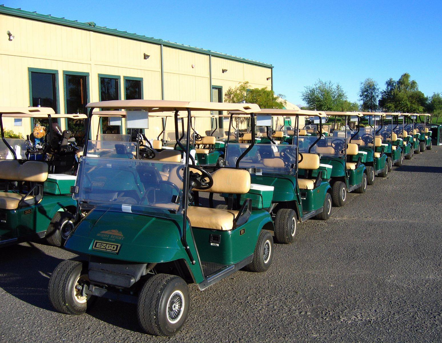 A row of golf carts lined up, ready for the next golf tournament